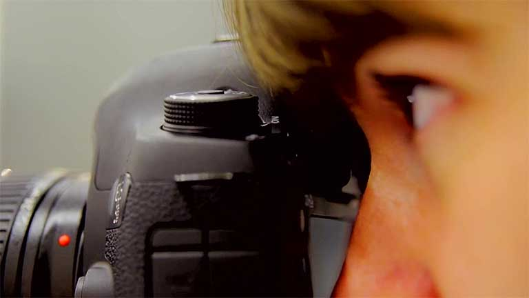 A close-up of a woman looking through the viewfinder of a camera.