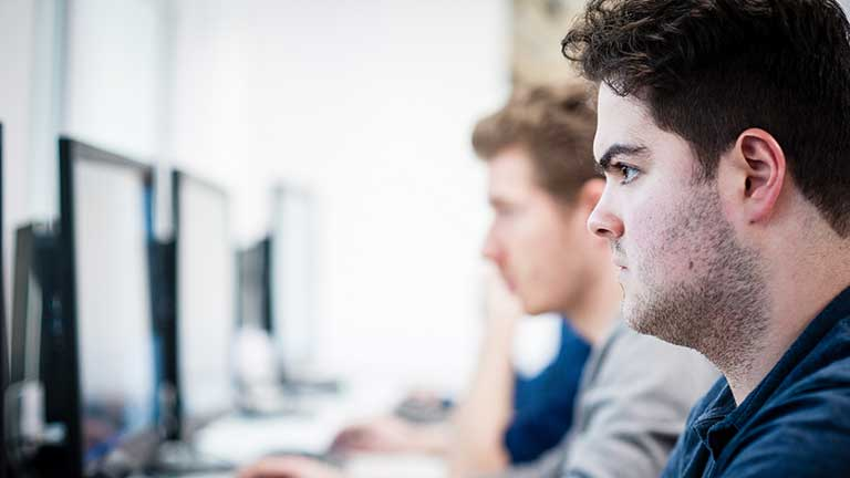 Student looking at a PC monitor.