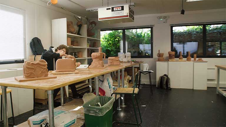Student working on clay models in a workshop.