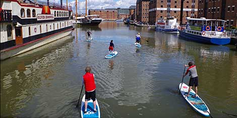 People stand up paddleboarding in Gloucester Docks.