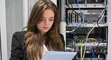 Woman standing next to computer servers.